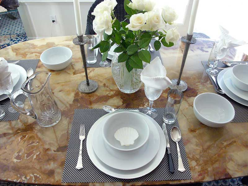 A Provençal lunch setting for four with white roses and large porcelain pasta bowls accented with decorative sea shells. Remove shells before serving!