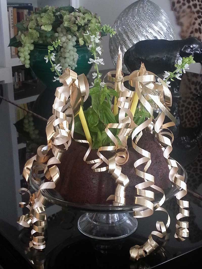 The Dump Bundt Cake in its singular glory dressed up in golden ribbons and decked out with flowering basil branches.