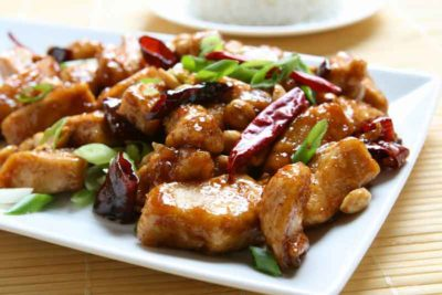 A closeup of Kung Pao Chicken served on a white plate