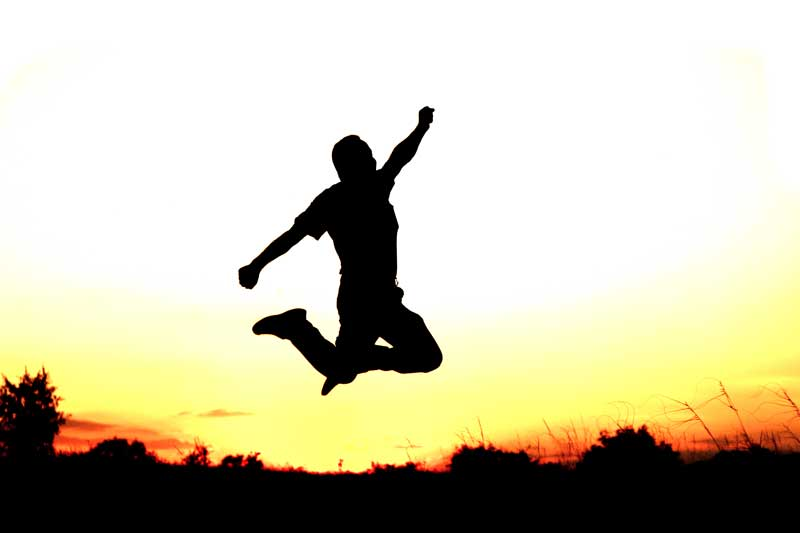 A silhouette of a man can be seen jumping triumphantly in an open field at sunset.