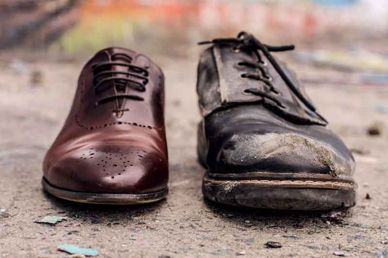 The polished shoe of a wealthy man next to the worn out shoe of a poor man.