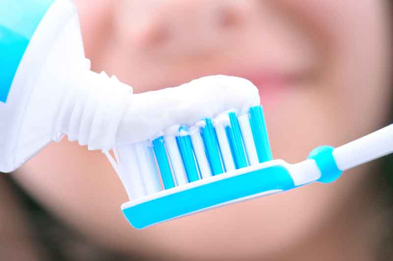 A woman prepares to brush her teeth